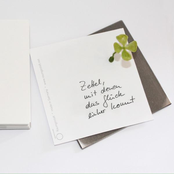 Notizblock Glückszettel von Raumgestalt - zwei Metallplatten mit Notizzetteln und kleinem grünen Kunststoff-Kleeblatt mit Magnet.