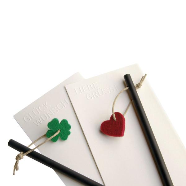 Geprägte Grußkarte mit Prägung Glückwunsch auf schlichtem cremefarbenen Papier - inklusive Umschlag, schwarz durchgefärbtem Bleistift und Glücksklee-Anhänger aus Filz.