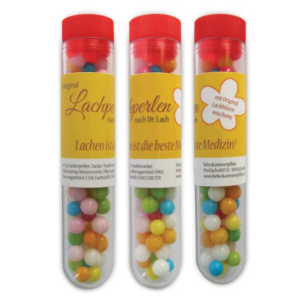 Lachperlen von liebeskummerpillen. Bunte Zuckerperlen in einem Reagenzglas.