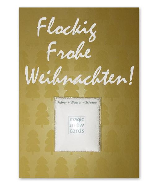 liebeskummerpillen Postkarte Flockig Frohe Weihnachten: goldene Postkarte mit Magic Snow Schneepulver.