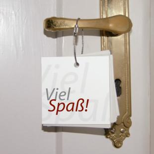 Türbotschaften von Raumgestalt - hier hängend an einem Türgriff mit dem Spruch Viel Spaß!.