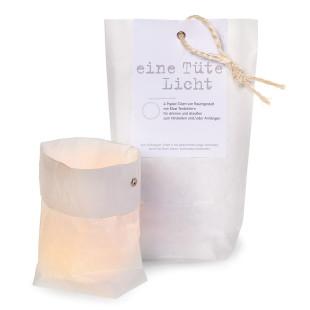 Eine Tüte Licht von Raumgestalt: vier kleine weiße Papiertüten, vier Maxi-Teelichter und ein wenig Draht verpackt in einer schönen Tüte.