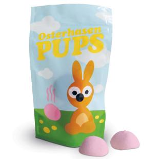 Osterhasen Pups von liebeskummerpillen: kleine Tüte mit Hasenmotiv, davor liegend zwei rosa Marshmallows.