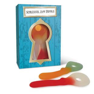 Schachtel befüllt mit Fruchtgummis und Aufschrift Schlüssel zum Erfolg von liebeskummerpillen